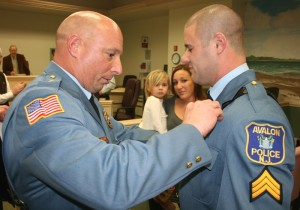 Chief William McCormick places a badge on Sergeant Glassford