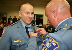 Captain Jeff Christopher receives his badge from Chief McCormick